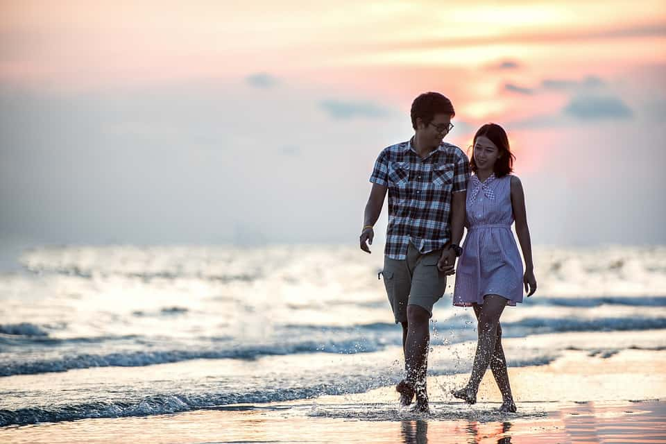 A couple walks down a beach holding hands. The digital nomad dream.