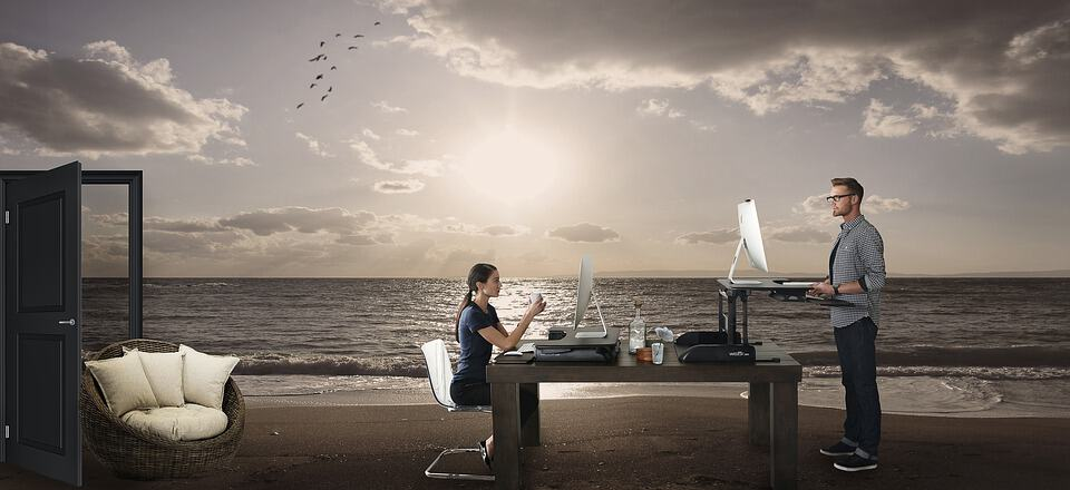 An image of a desk on a beach, the ideal work location for some digital nomads