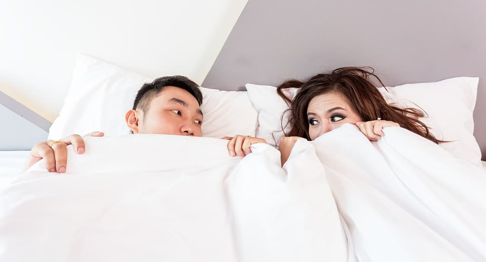 A couple in bed possibly dating, possibly insane.