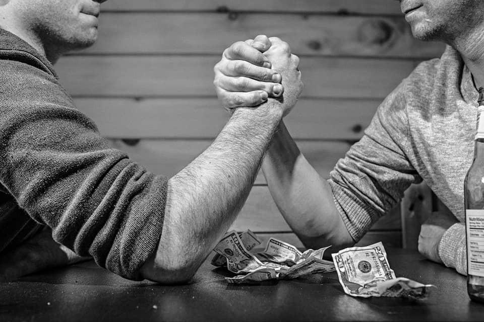 People arm wrestling over money.