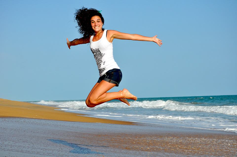A woman jumps for joy because she's ready to quit her job.