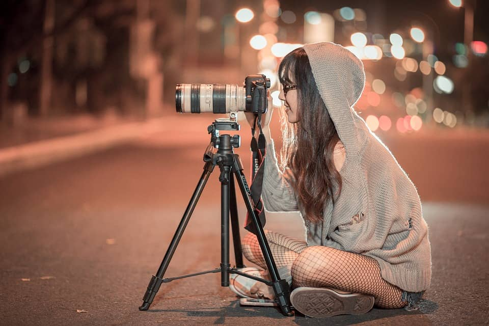 A woman takes a photo with a Canon camera in the middle of the street.