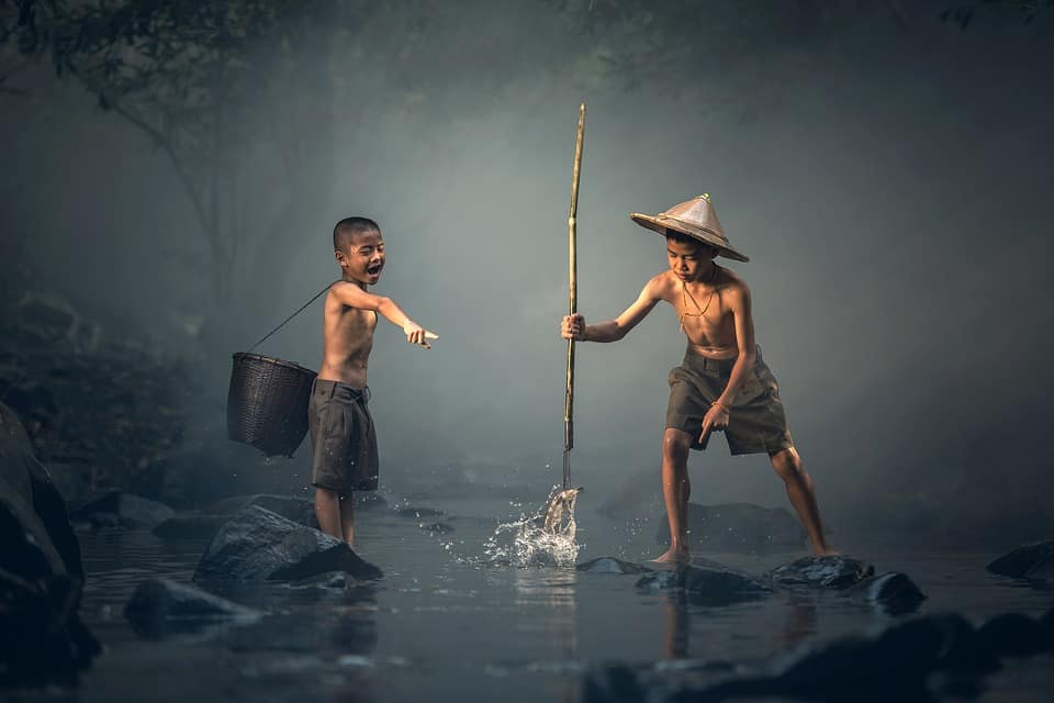 Two Thai kids fishing in a river.