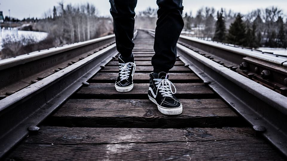A digital nomad's shoes on train tracks.