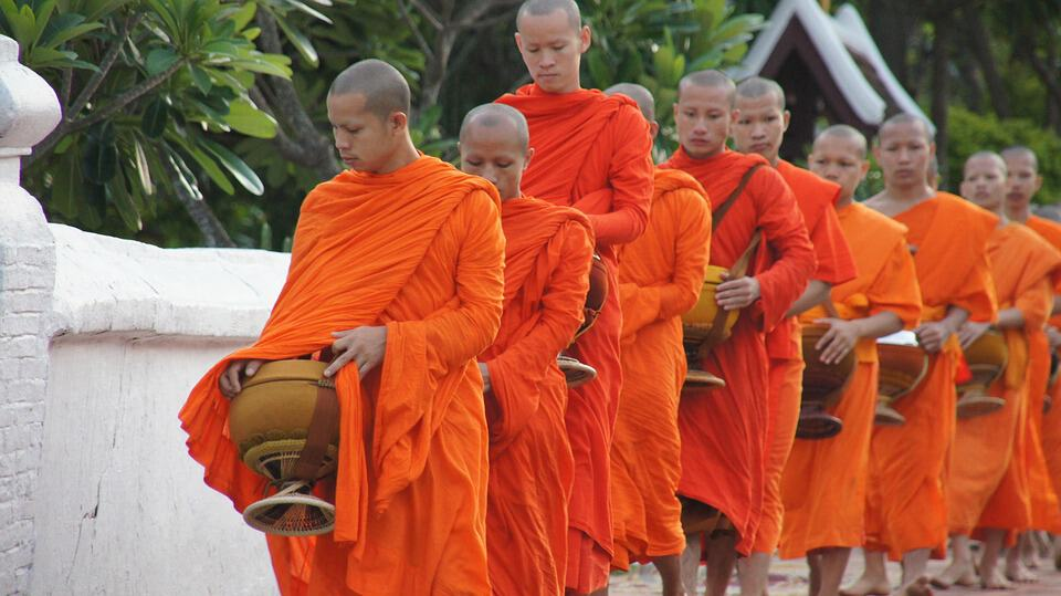 Buddhist monks queue for alms in Laos' second city.