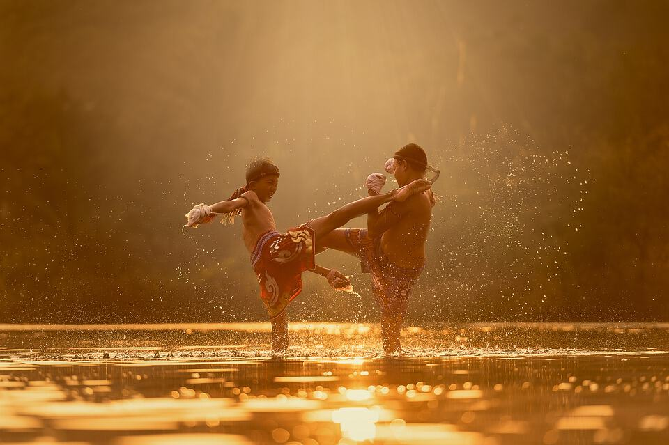 Two children engage in a bout of Muay Thai in a river